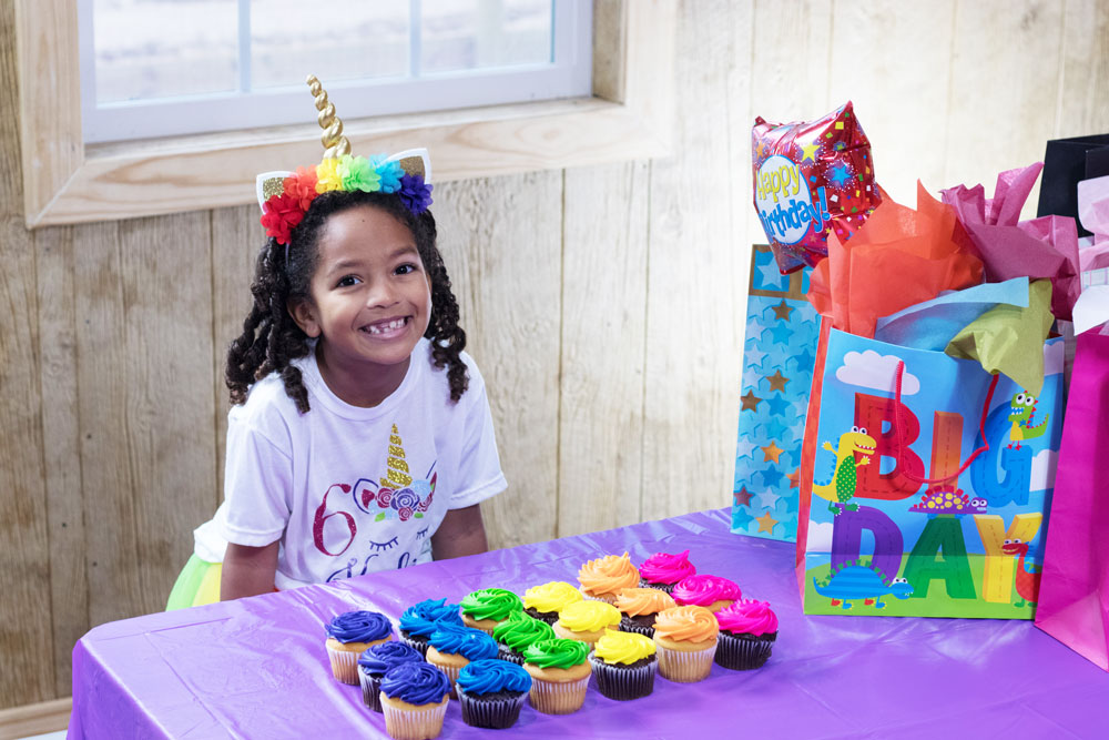 Young Girl With Cupcakes At Birthday Party