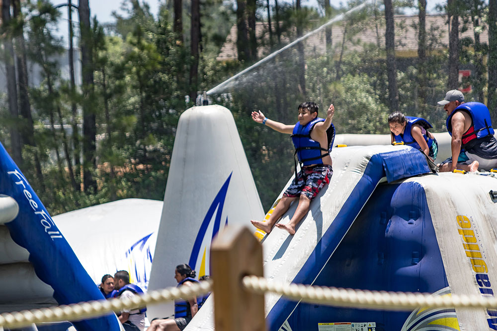 Guests Riding Wild Isle Inflatable Slides